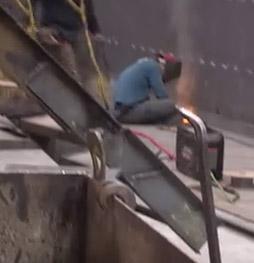 man welding side of ship